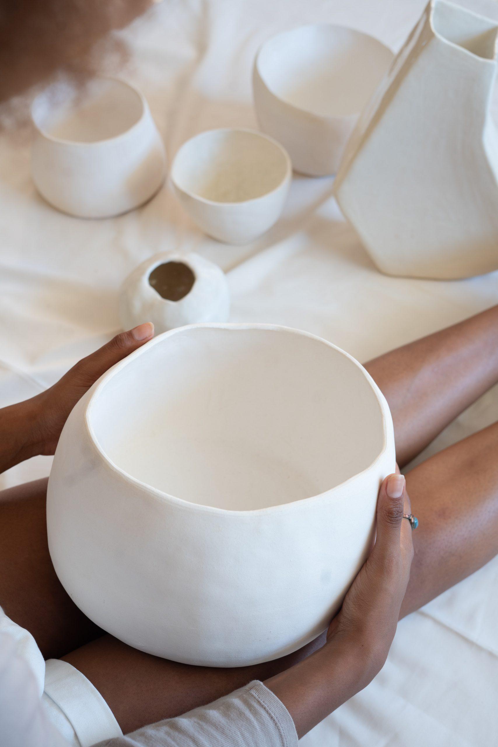 femme tenant un bol de poterie